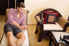 Young man in a hotel room using a phone Royalty Free Stock Image