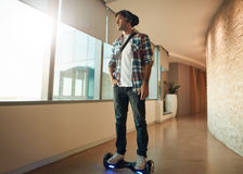 Young man on a hover board in office corridor Stock Images