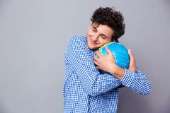 Young man hugging globe Royalty Free Stock Images