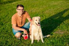 Young man hugging golden retriever dog in summer outdoors. Portrait of young man sitting hugging with golden retriever dog. Friendship, pet and human. Man Stock Images