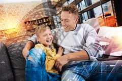 Young man hugging his cheerful son and laughing with him. Cheerful relatives. Emotional caring attentive father looking at his little happy son and hugging him Royalty Free Stock Photos