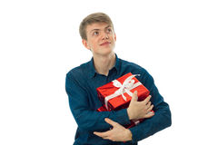 Young man hugging his gifts. Portrait of happy young man hugging his gifts and looking away isolated on white background Royalty Free Stock Photos