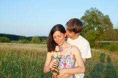 Young man hugging his girlfriend. Loving young men hugging his girlfriend with rose in her hands stock photo