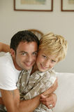 Young man hugging little boy Stock Photos