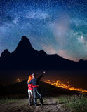 Young man hugging red-haired woman and shows on stars and Milky way in beautiful starry sky at night Stock Image