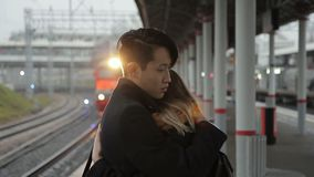 Young man is hugging woman standing at railway station outdoors. multiethnic. Enamored people cuddle warmly, embracing each other with hands and touching with stock video