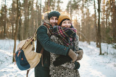 Young man hugs his girlfriend in winter forest Stock Photo