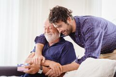 Free Young Man Hugs The Uncle Old Man Warmly Inside The House, Son Happy And Love His Father Or Grand Father With Gift Box Concept Royalty Free Stock Image - 171783356