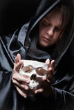 Young man with human skull in the hand Royalty Free Stock Photo