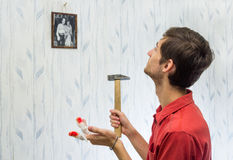 The young man hung pictures on the wall, improving interior Stock Photo