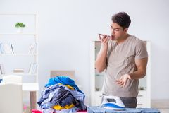 The young man husband doing clothing ironing at home. Young man husband doing clothing ironing at home Stock Image