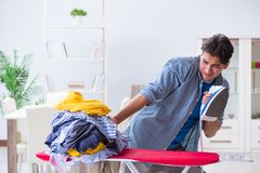 The young man husband doing clothing ironing at home. Young man husband doing clothing ironing at home Stock Photography