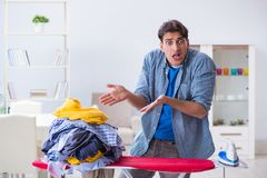 The young man husband doing clothing ironing at home. Young man husband doing clothing ironing at home Royalty Free Stock Image
