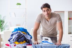 The young man husband doing clothing ironing at home. Young man husband doing clothing ironing at home Royalty Free Stock Images