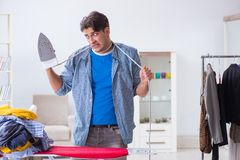 The young man husband doing clothing ironing at home. Young man husband doing clothing ironing at home Royalty Free Stock Photography