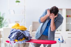 The young man husband doing clothing ironing at home. Young man husband doing clothing ironing at home Royalty Free Stock Photos