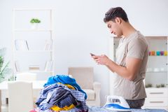 The young man husband doing clothing ironing at home. Young man husband doing clothing ironing at home Stock Images