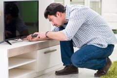 The young man husband repairing tv at home royalty free stock images