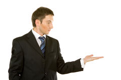 Young man i. Handsome young man in a suit presenting or showing you something Stock Photo