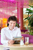 Young man in ice cream parlor Royalty Free Stock Images