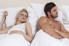 Young man ignoring woman in bed Royalty Free Stock Image
