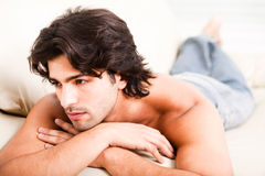 Young man imagine by laying on the sofa. Man looking right corner by lying on couch in his home stock image