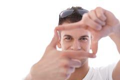 Young man imitating photographing smiling Stock Image