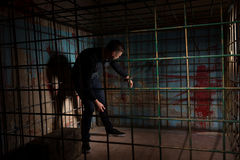 Young man imprisoned in a metal cage with a blood splattered wal Royalty Free Stock Photography