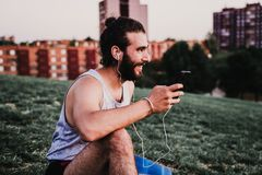 Free Young Man In A Park Listening To Music On Mobile Phone And Headset After Practicing Yoga Sport. City Background. Healthy Lifestyle Royalty Free Stock Images - 163762809