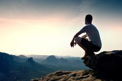Young Man In Black Sports Pants And Grey Shirt Is Sitting On Cliff S Edge And Looking To Misty Valley Bellow Royalty Free Stock Images