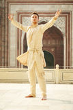 Young man in indian clothes. Confident young man with open arms wearing kurta, standing barefooted in Taj Mahal, India royalty free stock image