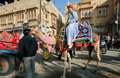 Young man in indian dress rides the camel on the street Royalty Free Stock Images