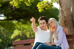 Young man indicating something to girlfriend. Royalty Free Stock Photography