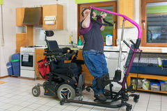Young man with infantile cerebral palsy. Young man with infantile cerebral palsy from birth complications using a patient lift to move from his bed to a royalty free stock photos