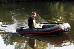 Young man in inflatable boat with fishing at river. Royalty Free Stock Image
