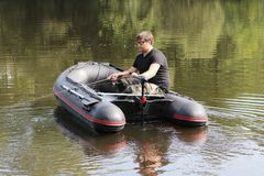 Young man in inflatable boat with fishing at river. Stock Photography