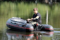 Young man in inflatable boat with fishing at river. Royalty Free Stock Photography