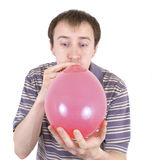 The young man inflates a balloon Stock Photography