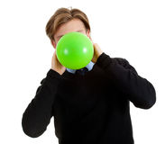 Young man inflating green balloon Royalty Free Stock Photography