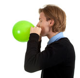 Young man inflating green balloon Royalty Free Stock Photos