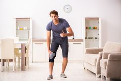 The young man with injured knee recovering at home stock image