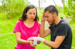 Young man with injured wrist sitting and getting bandage compression wrap from female, outdoors environment Stock Images