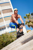 Young man with inline skates in summer outdoor royalty free stock images