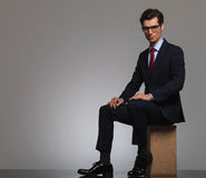 Young man ins suit and tie wearing glasses is sitting Royalty Free Stock Photography