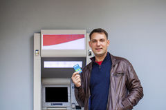 Young man inserting a credit card to ATM Royalty Free Stock Photos