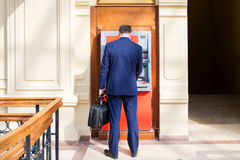 Young man inserting a credit card to ATM Royalty Free Stock Photography