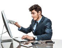 Young man inserting a dollar into a monitor, paying online concept Royalty Free Stock Images
