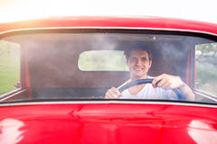 Young man inside red vintage pickup truck Stock Images