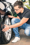 Young man inspecting a tire of a luxury car for insurance Royalty Free Stock Photography