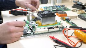 Young man installing CPU cooler fan on motherboard. Engineer assembling CPU in repair shop stock footage